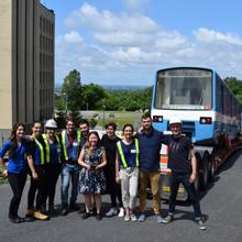 Des membres du comité étudiant Station Polytechnique posent près de la voiture de métro MR-63, peu avant son insertion dans les pavillons Lassonde.