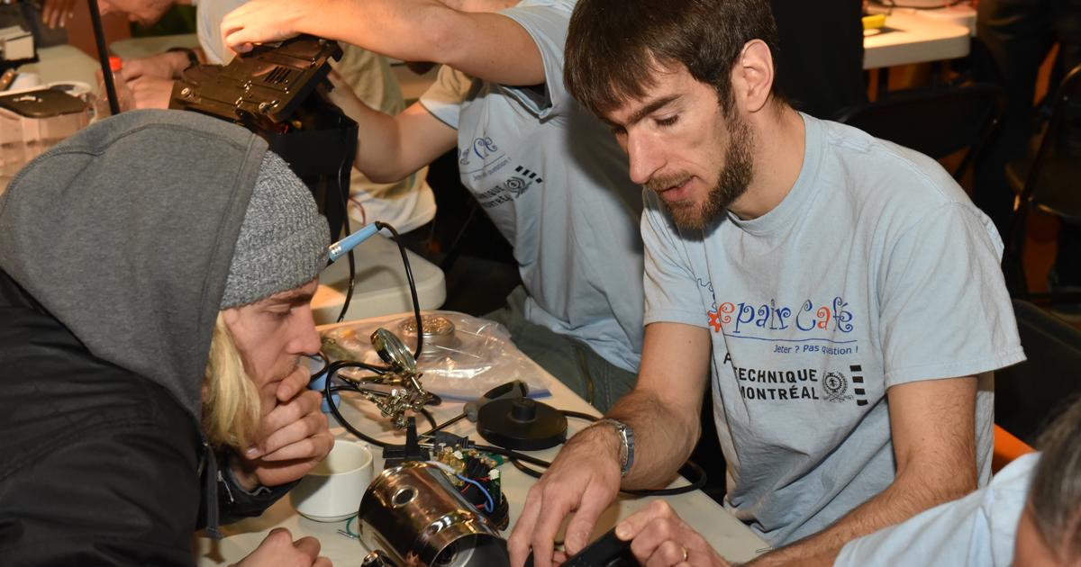Un bénévole et une participant tentent de remettre un appareil électrique en état de marche.
